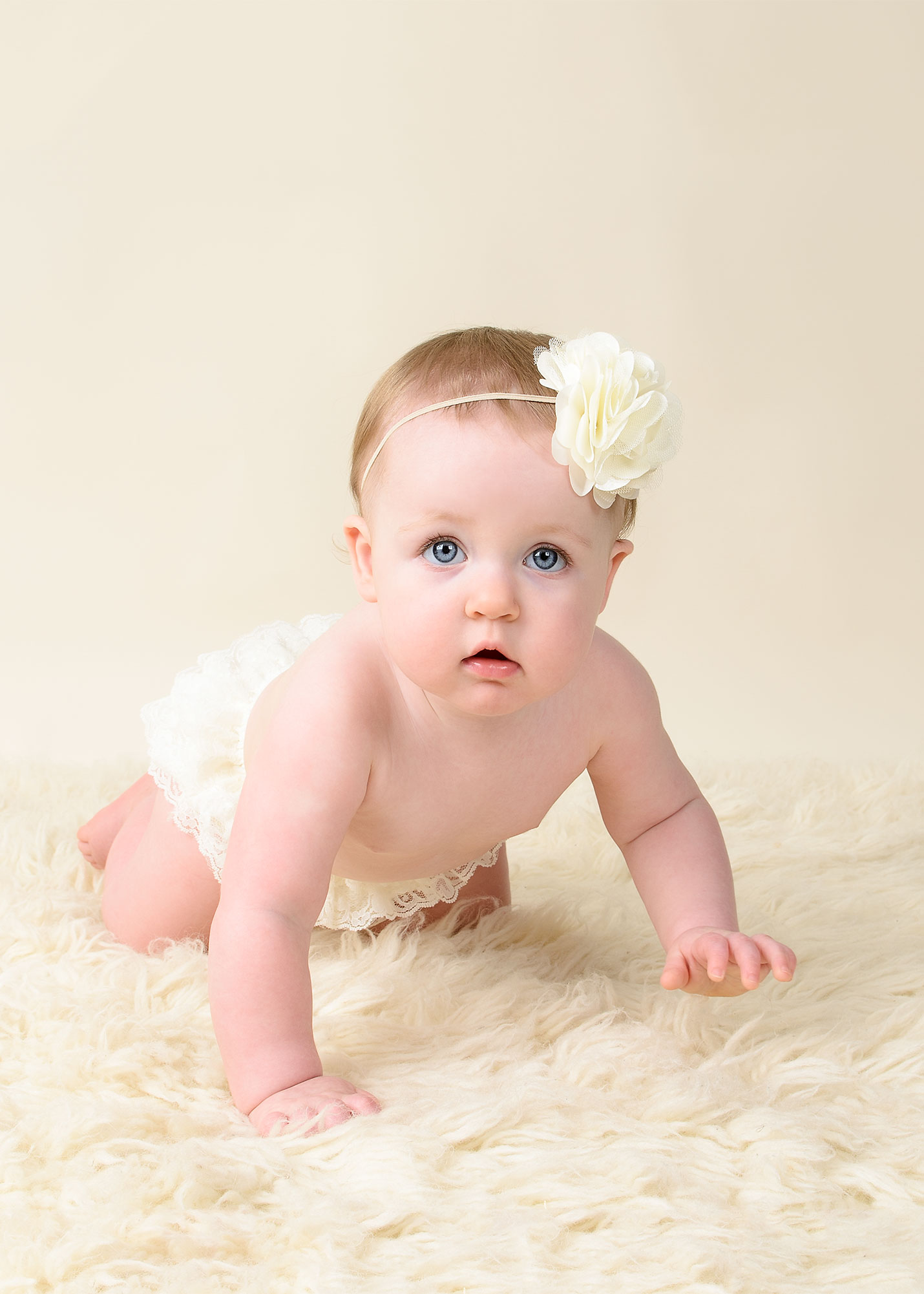 Portrait of little girl crawling on beige background in magnolia moments professional photography studio near me
