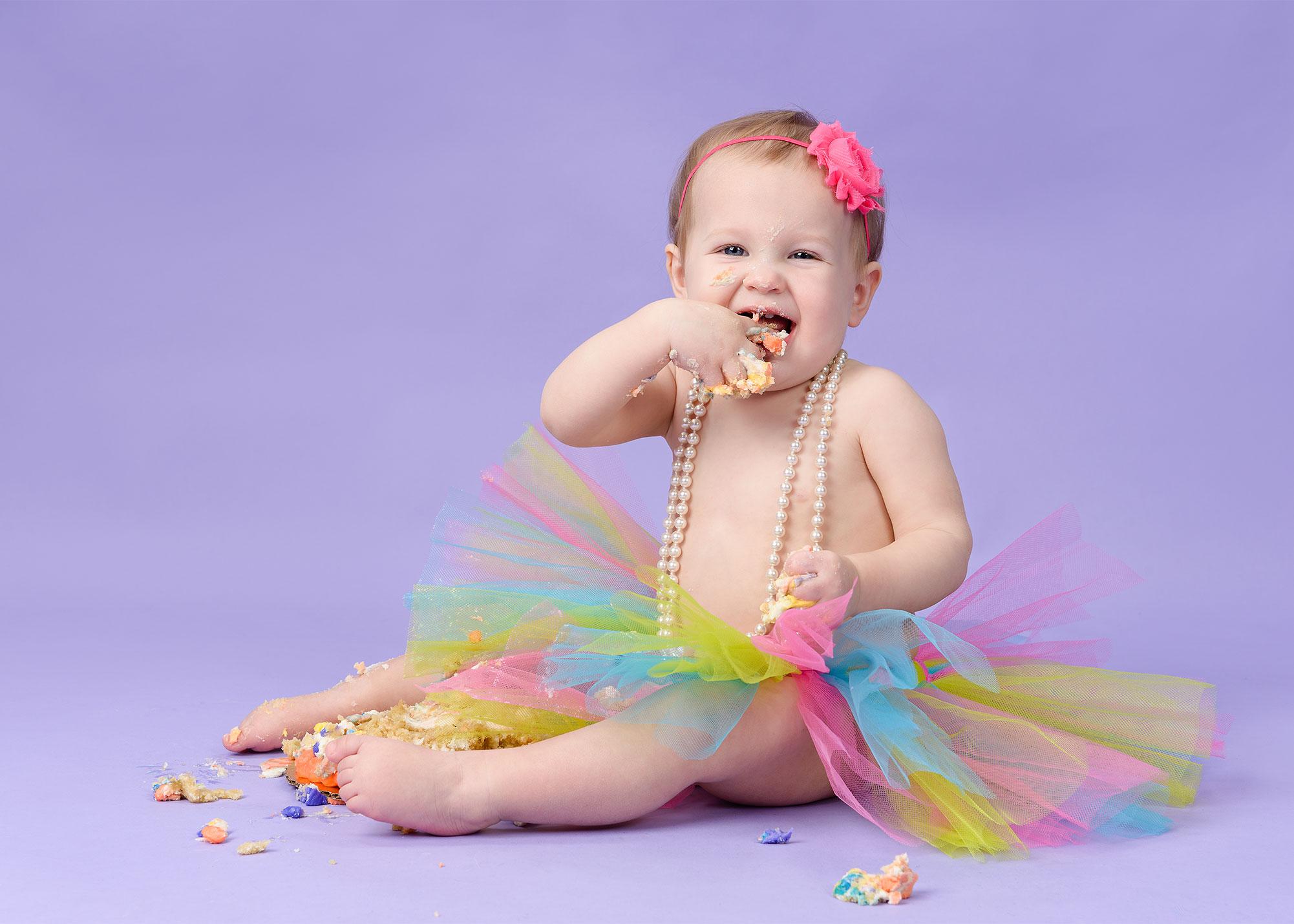 Cake smash 1st birthday portrait rainbow tutu on purple by