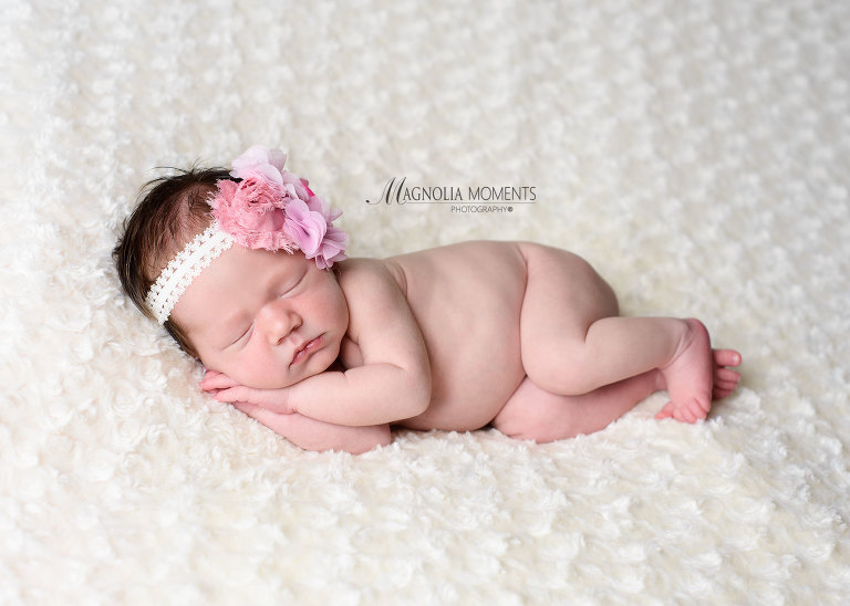 Adorable newborn baby girl posing for her newborn photography session by one of the professional photographers