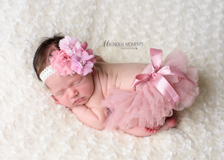 Newborn baby girl dressed in pink newborn baby clothes for her newborn photoshoot by photographers near me. Newborn baby pic taken by Evan Pollock of Magnolia Moments Photography outside of Philadelphia Pennsylvania Phoenixville newborn photographer