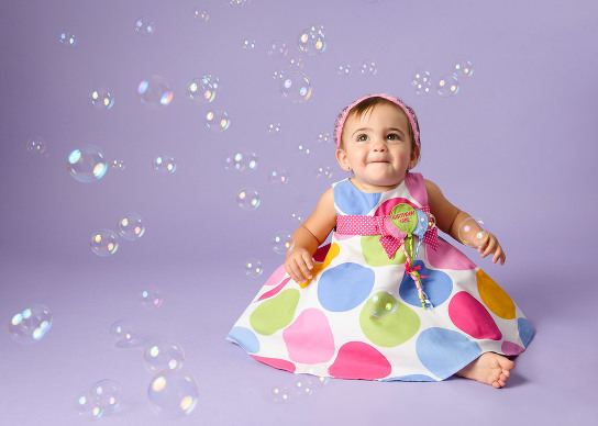 Professional baby photography near me of little girl in polka dot dress surrounded by bubbles by