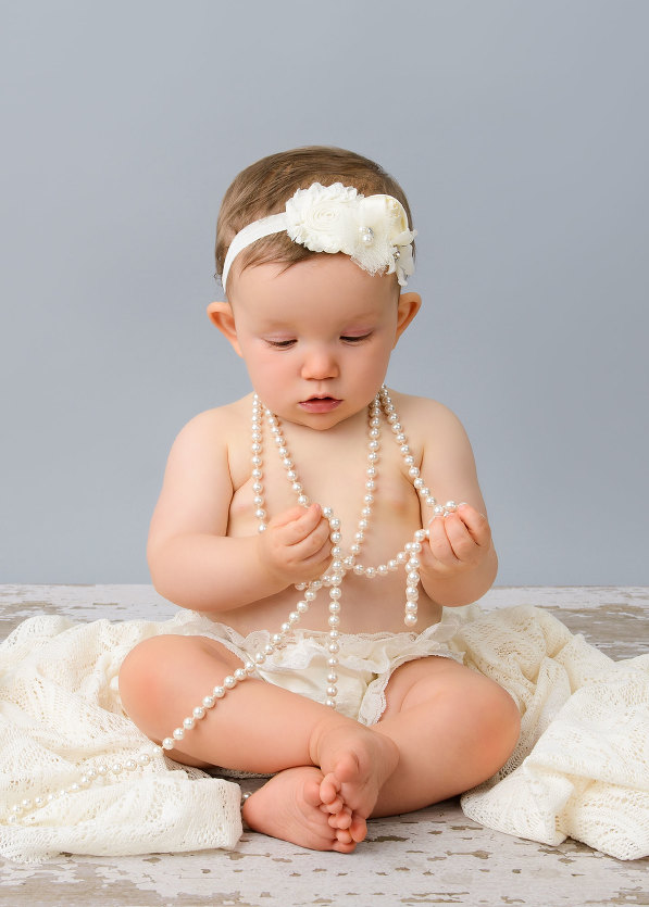 Professional baby photography of baby girl wearing pearls and white lace on barn floor by evan