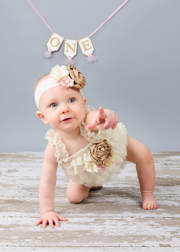 1st birthday photography of baby girl in white lace with brown white and pink flowers in