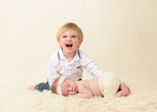 Professional newborn photoshoot of baby and his very excited brother by evan pollock of magnolia moments