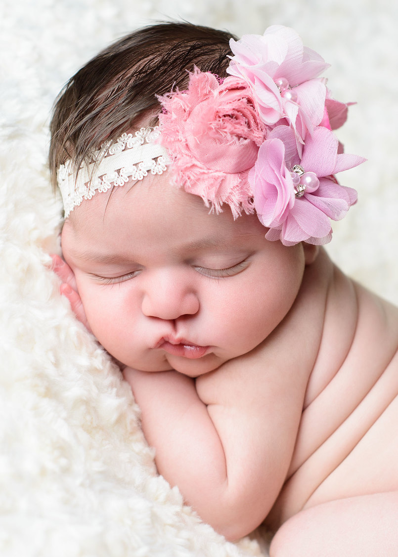 Professional newborn portrait of baby girl sleeping on hand with big pink flowers in hair by
