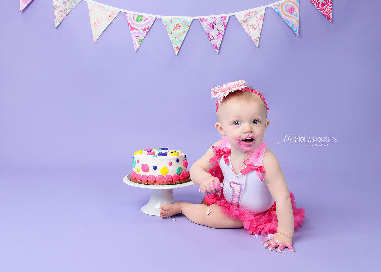Baby girl dressed in pink cake smash outfit on purple background who is very excited about her smash cake taken by Evan Pollock who does Cake Smash and professional photography near me