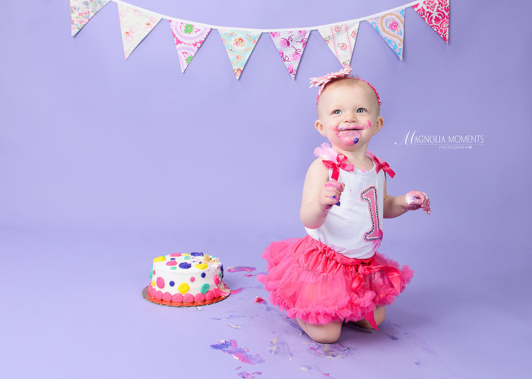 Cute baby girl in adorable cake smash outfit on purple background with smash cake icing all over her face taken by Evan Pollock of Magnolia Moments Photography who does child photography near me in her photography studios near me.