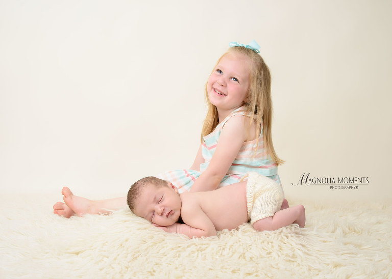 Newborn baby boy with big sister posed on cream during newborn photoshoot by Magnolia Moments Photography near me.