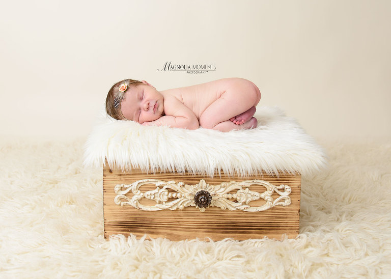 Newborn baby girl posed on fur on antique drawer during her newborn photoshoot by Evan Pollock of Magnolia Moments Photography, who does professional photography near me.