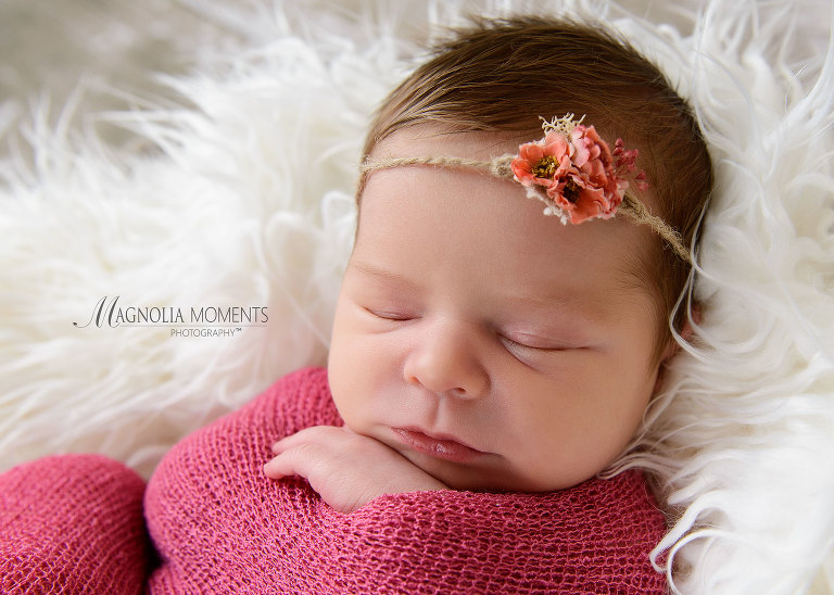 Newborn baby pic of tiny girl wearing pink wrap and headband during her newborn photoshoot by one of the photography studios near me, Magnolia Moments Photography.