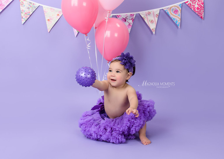 Beautiful 1 year old girl on purple taken during her Cake Smash session by Evan Pollock of Magnolia Moments Photography