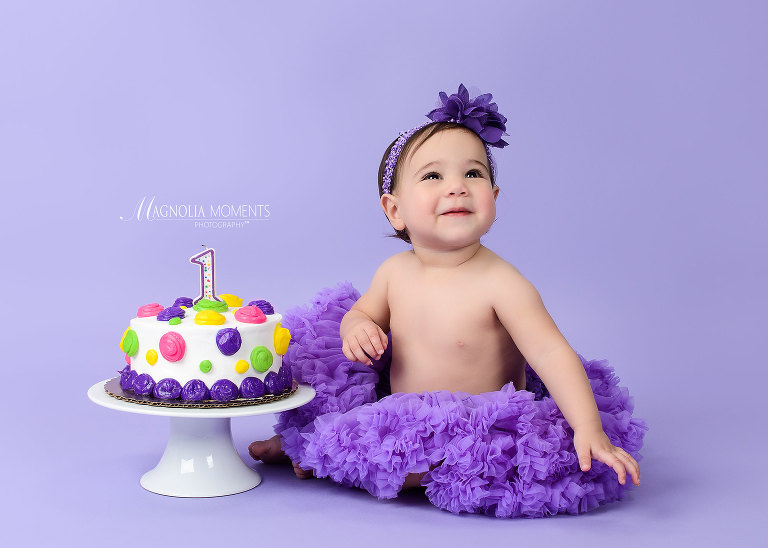 Birthday girl on purple with her smash cake during her Cake Smash session by Magnolia Moments Photography who does child photography near me