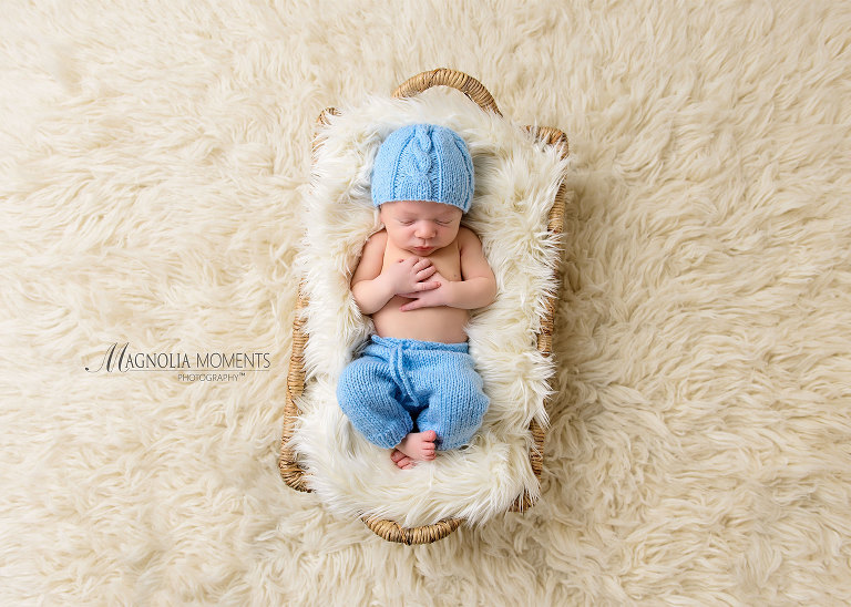 Newborn baby boy in blue newborn baby clothes photographed by Evan Pollock of Magnolia Moments Photography photography studio near me. Yardley newborn photographer