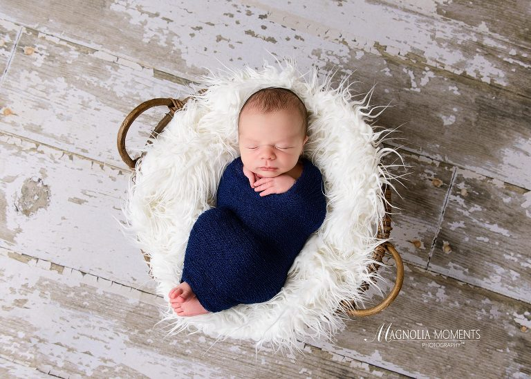 Newborn baby pic of boy in navy wrap on barn floor photographed by Evan Pollock of Magnolia Moments Photography during his newborn photoshoot. Yardley newborn photographer