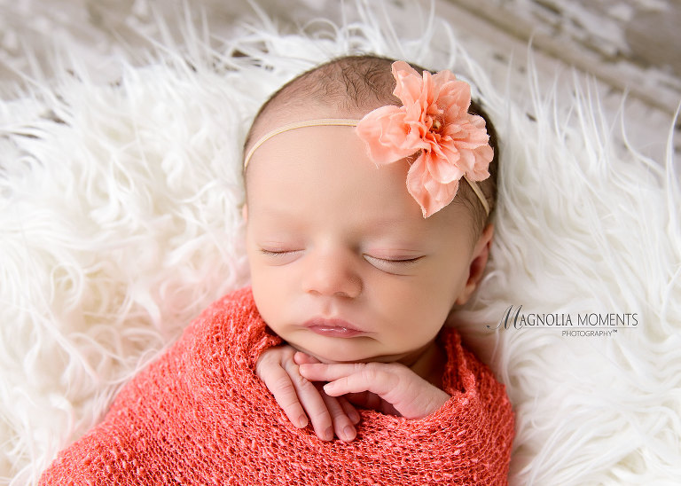Closeup of newborn girl in pink wrap with flower for her newborn baby clothes for her photoshoot by Evan Pollock one of the professional photographers near me - Collegeville newborn photography