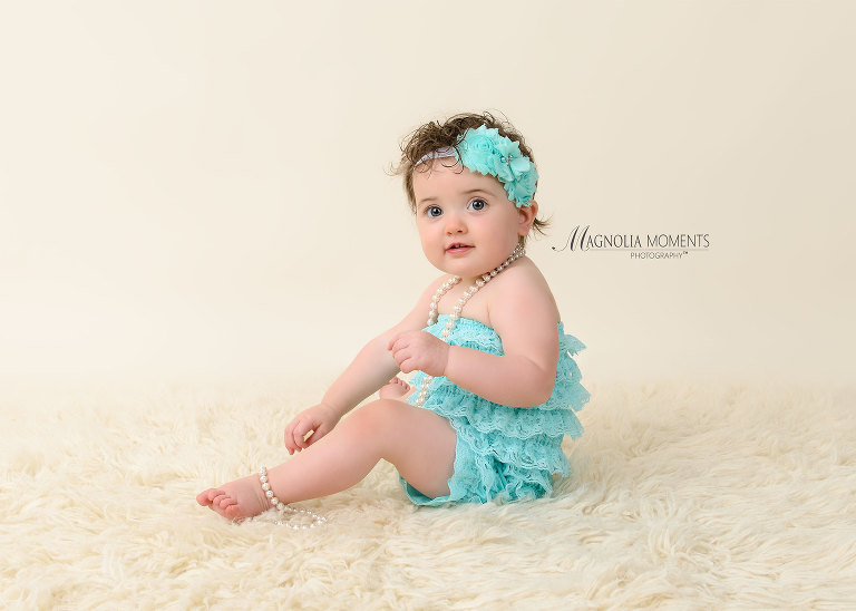 Beautiful baby girl in teal ruffle cake smash outfit for her 1st birthday cake smash session by Evan Pollock of Magnolia Moments Phtography
