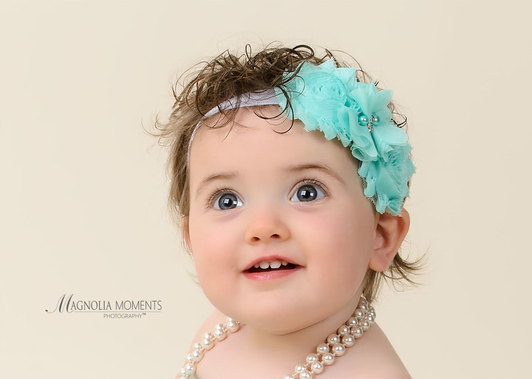 Closeup of one year old baby girl in teal headband taken by Evan Pollock for 1st birthday cake smash session