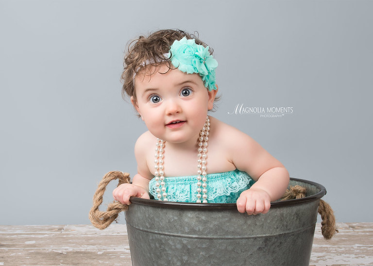 Baby girl dressed in teal and posed in a bucket during her 1st birthday cake smash by Evan Pollock of Magnolia Moments Photography a professional studio near me