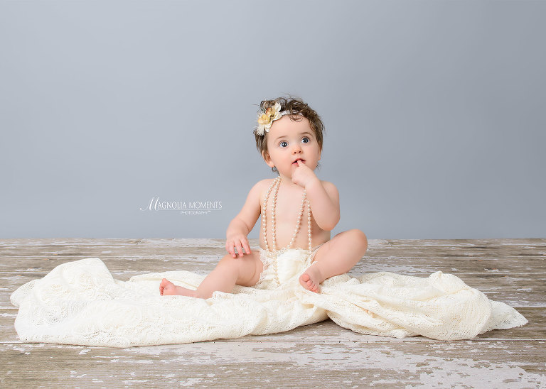 Baby girl in white photographed on barn floor for her 1st year portrait session by Evan Pollock of Magnolia Moments Photography who does professional photography near me