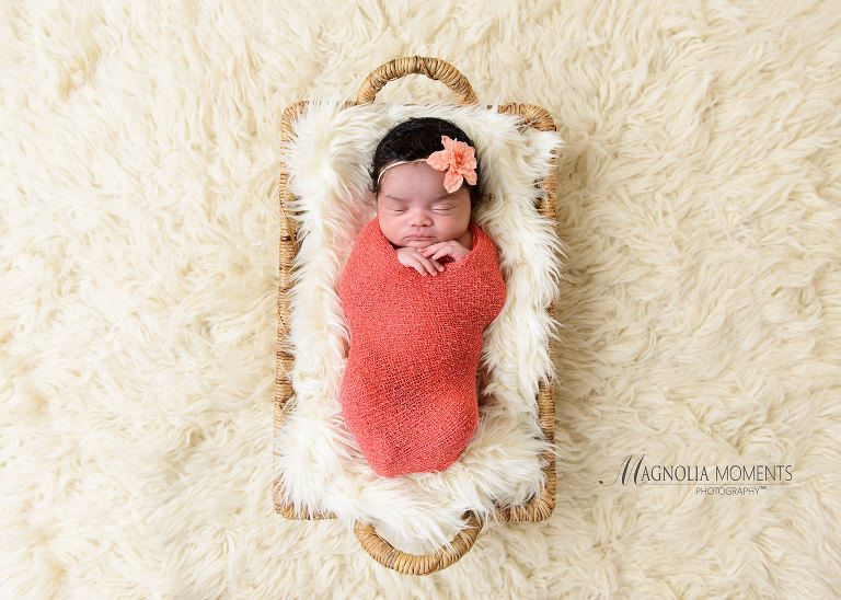 Newborn baby girl wrapped in coral wrap on fur lined basket during her newborn photography session by Magnolia Moments Photography a professional photographer near me.