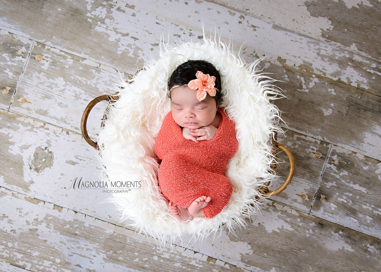 Adorable newborn baby girl in coral wrap in basket on barn floor photographed by Evan Pollock of Magnolia Moments Photography during her newborn photography session near me.