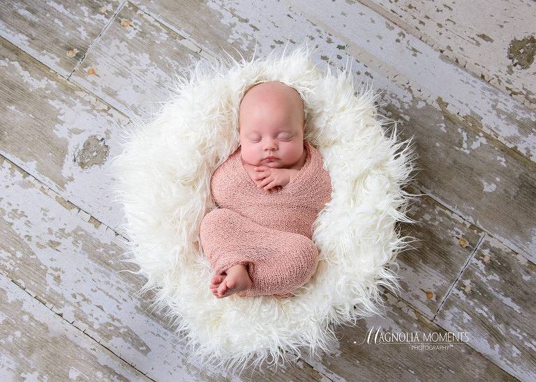 Newborn baby girl wrapped in pink and posed in fur lined basket on barn floor during her newborn photoshoot session by Evan Pollock of Magnolia Moments Photography