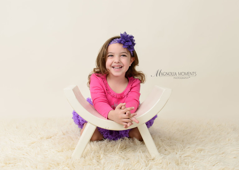 Beautiful 4 year old gild in pink and purple outfit photographed on curved bench on fur floor by Evan Pollock of Magnolia Moments Photography a professional photographer near me. Collegeville child photographer.