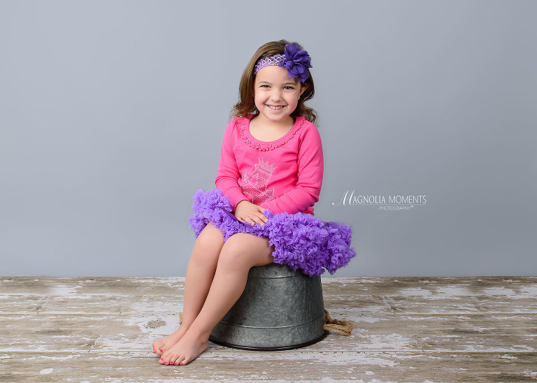 4 year old girl in purple and pink seated on bucket on barn floor during her birthday photography session by Magnolia Moments Photography