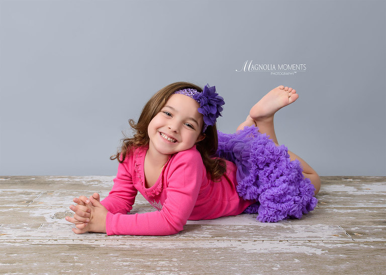 Pretty 4 year old girl laying on barn floor in purple tutu and pink shirt during her 4 year birthday photography session by Evan Pollock of Magnolia Moments Photography a photography studio near me. Collegeville child photographer.