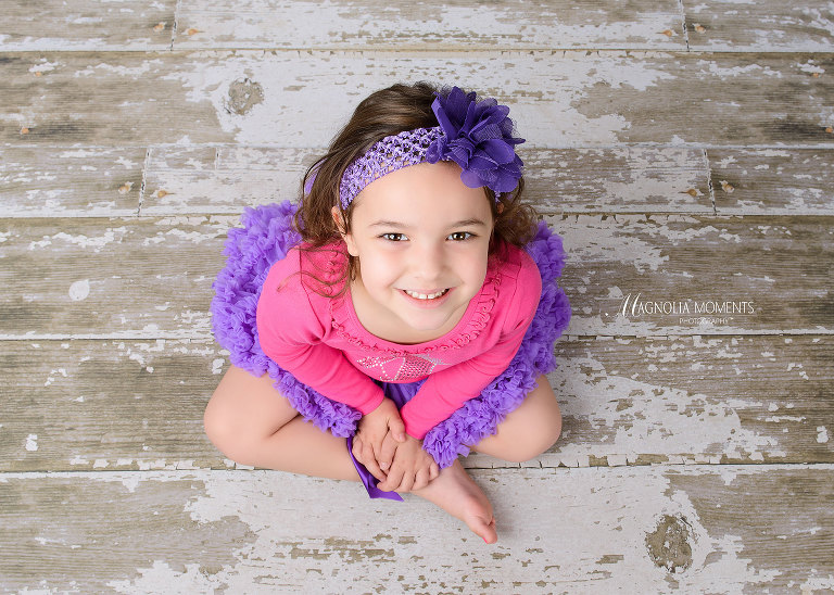 Sweet girl seated on barn floor in purple tutu and pink shirt photographed by Evan Pollock of Magnolia Moments Photography one of the photographers near me. Collegeville child photographer.