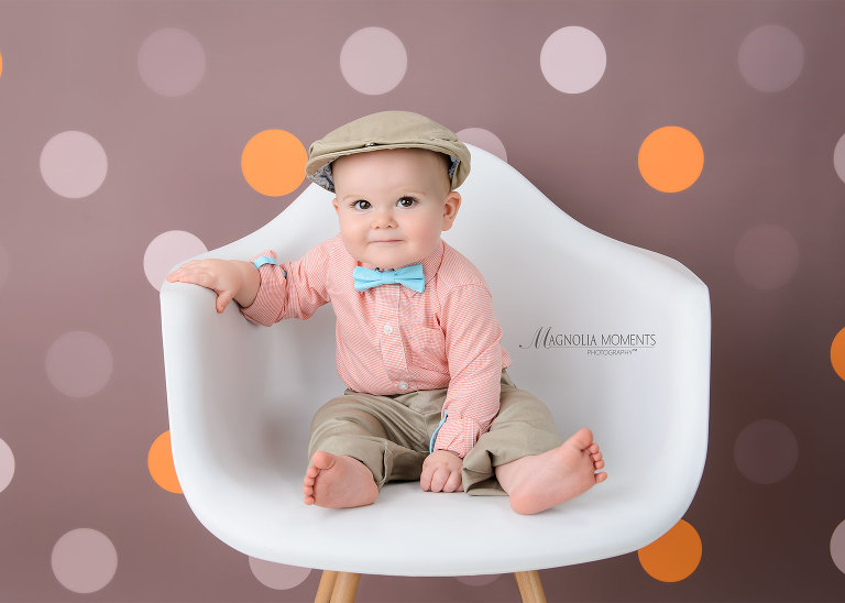 Cute one year old baby boy wearing cap and blue bow tie for his cake smash outfit during his first birthday portrait session by Evan Pollock of Magnolia Moments Photography a professional photographer near me. Philadelphia baby photographer
