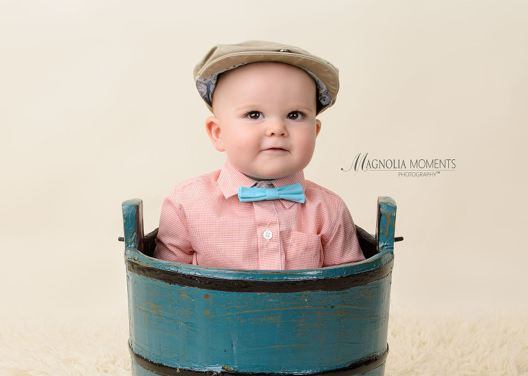 Sweet baby boy wearing cap and blue bow tie in blue bucket for first year portraits by Magnolia Moments Photography a photography studio near me. Philadelphia baby photographer
