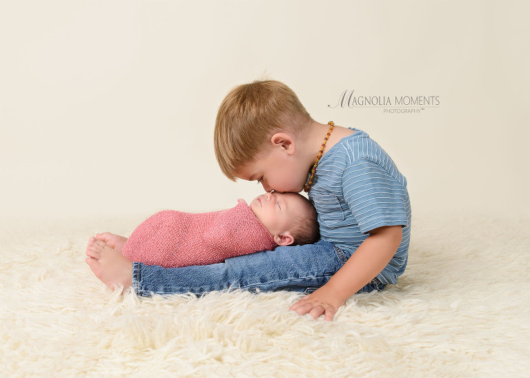 Sweet newborn baby girl in pink with her big brother kissing her during her newborn photo session by Evan Pollock of Magnolia Moments Photography a professional photographer near me. Aston newborn photographer.