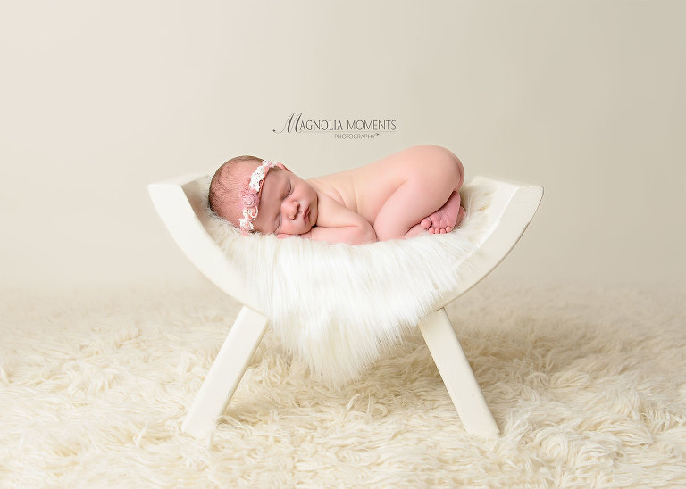 Precious newborn girl on curved bench against cream backdrop for her newborn session by Evan Pollock of Magnolia Moments Photography a photography studio near me. Aston newborn photographer.