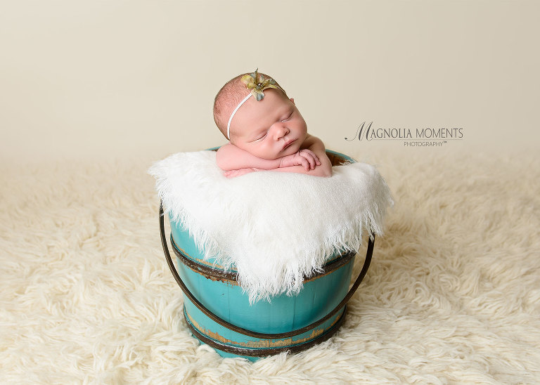 Sweet baby girl sleeping in team bucket with fur and flower headband during her newborn photoshoot by Evan Pollock of Magnolia Moments Photography a professional photographer near me. Aston newborn photographer.