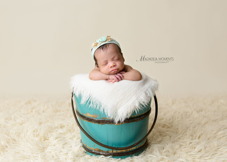 Newborn girl in teal bucket with headband during her newborn photoshoot by Evan Pollock of Magnolia Moments Photography a professional photography studio near me. Boyertown newborn photographer