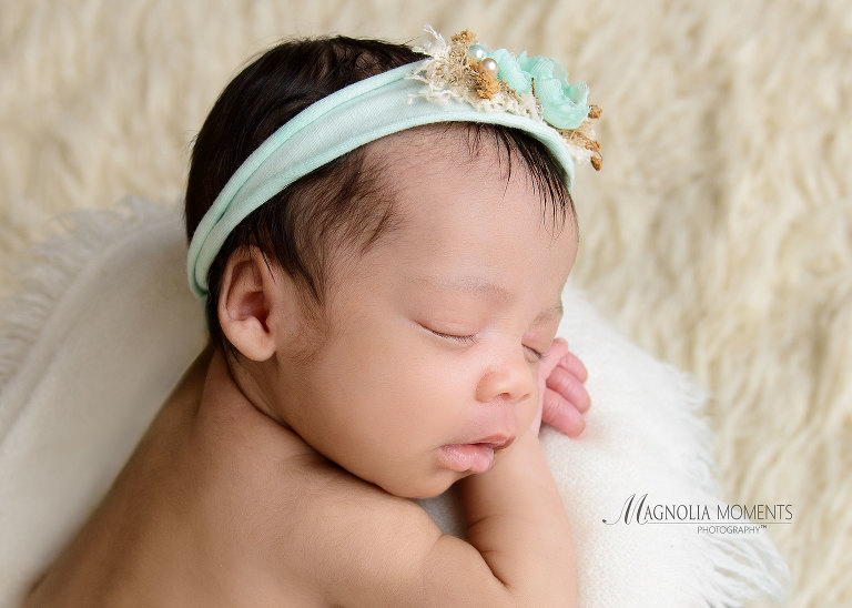 Closeup photo of newborn girl sleeping on white blanket with teal headband taken by Evan Pollock of Magnolia Moments Photography who does professional photography near me. Boyertown newborn photographer