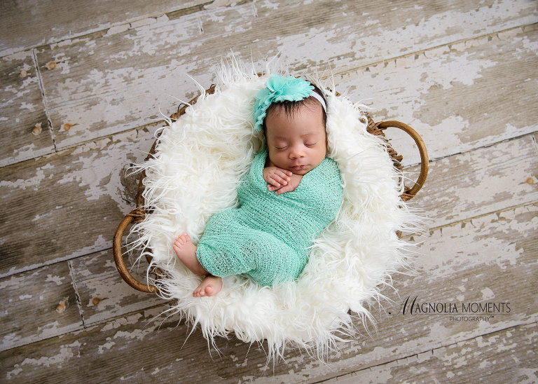 Newborn baby girl wrapped in teal with teal headband sleeping in a basket on barn floor during her newborn portrait session by Evan Pollock of Magnolia Moments Photography a professional studio near me. Boyertown newborn photographer
