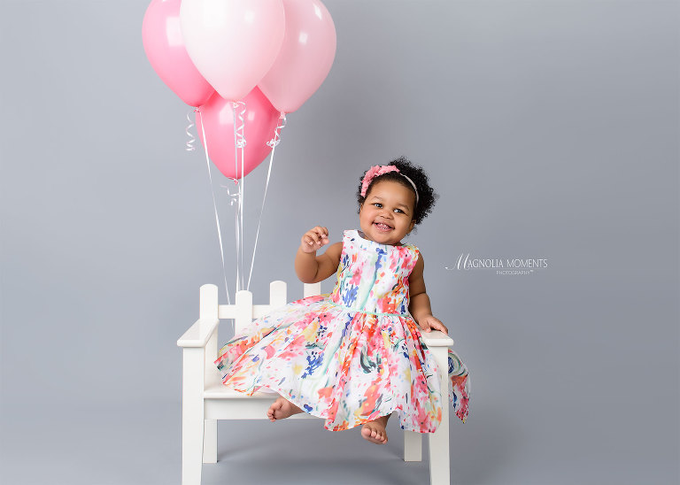 Baby girl in floral dress on white bench with pink balloons during her 1st birthday portrait session by Magnolia Moments Photography a photography studio near me.