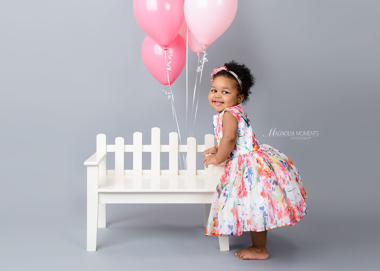 1st birthday portraits of sweet baby girl in floral dress with white bench and pink balloons photographed by Evan Pollock of Magnolia Moments Photography a family photographer near me.