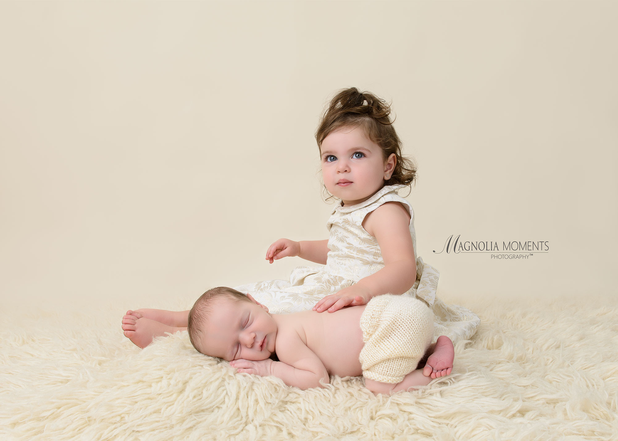 Newborn baby boy with big sis posed on cream fur by Evan Pollock of Magnolia Moments Photography who does professional photography near me. Blue Bell newborn photographer.