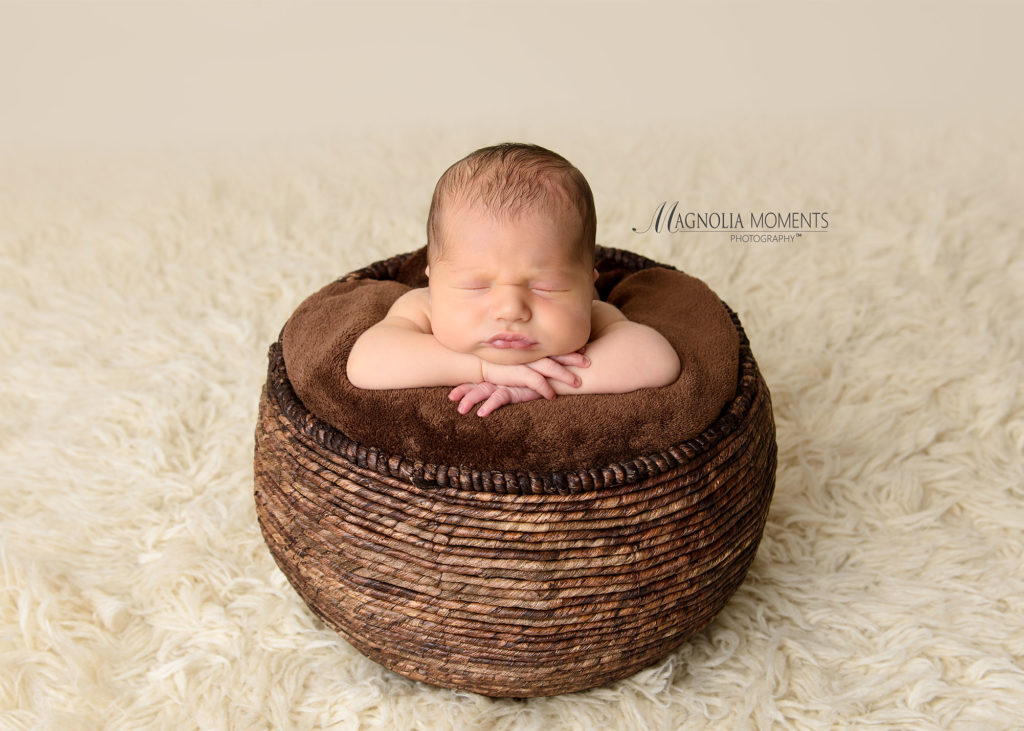 Tiny baby boy posed in brown basket with his chin on his hands for his newborn photoshoot by Magnolia Moments Photography one of the professional photography studios near me.