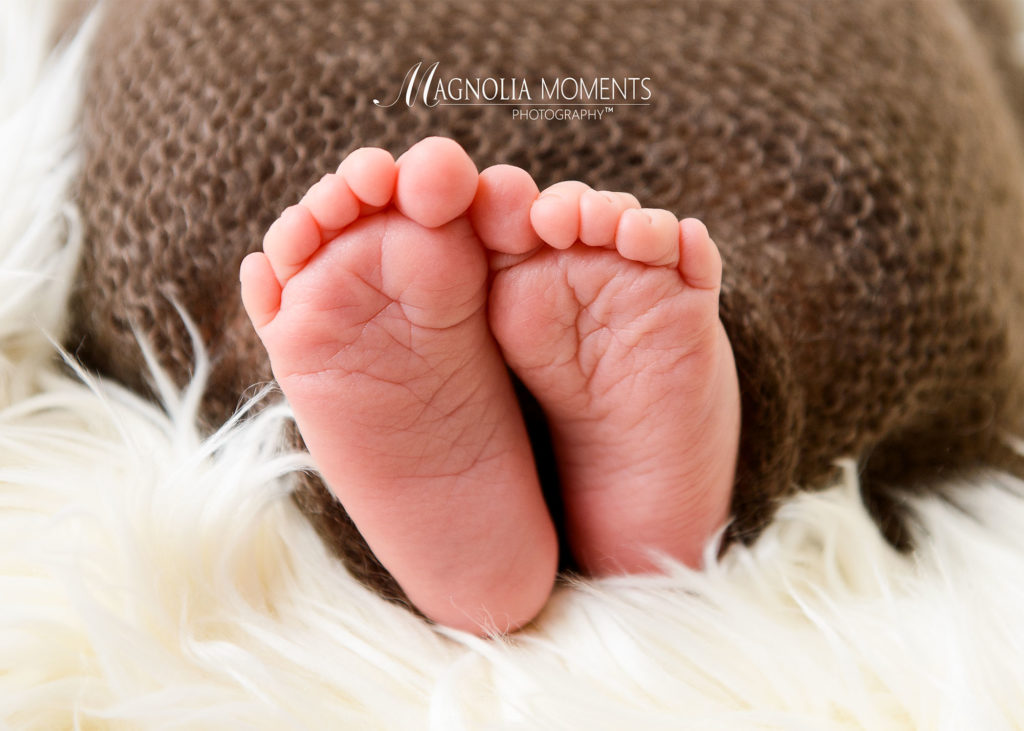 Closeup of tiny newborn feet with brown background taken by Evan Pollock of Magnolia Moments Photography one of the photography studios near me.