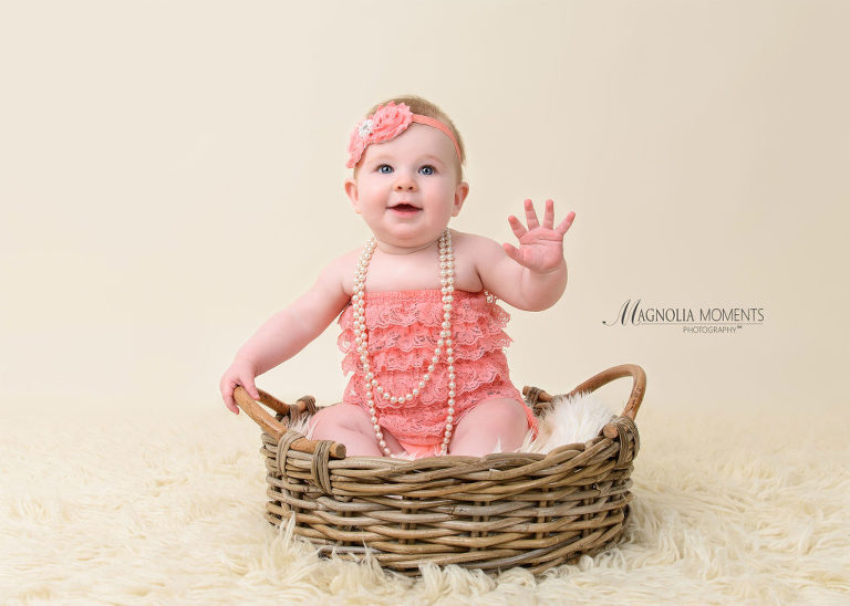 adorable baby girl dressed in pink ruffled romper and headband during her 6-month portrait session by Evan Pollock of Magnolia Moments Photography a baby and child photographer near me. Mont Clare baby photographer.