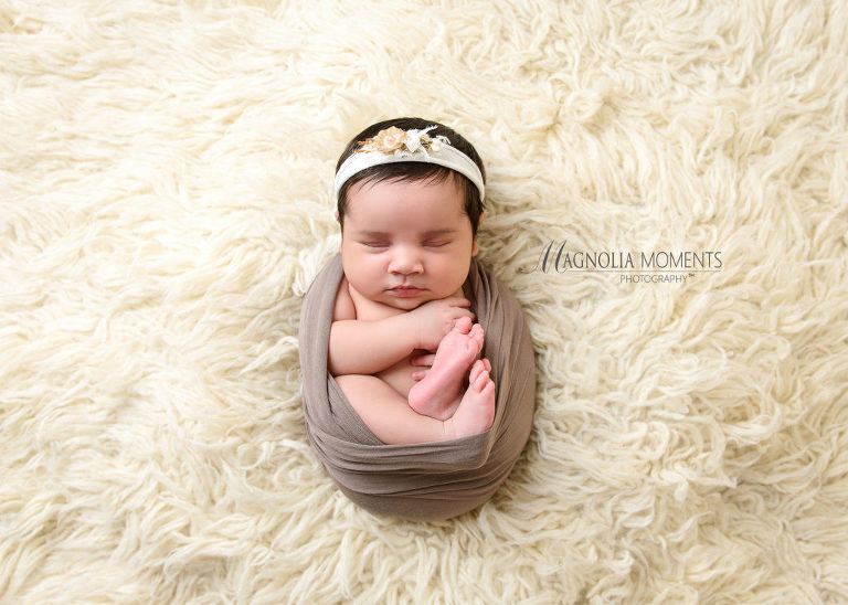 Photo of sweet newborn girl all curled  up with taupe wrap and cream flower headband on fur floor during her newborn photoshoot by Evan Pollock of Magnolia Moments Photography who does newborn photography near me. Philadelphia Newborn Photography Session.