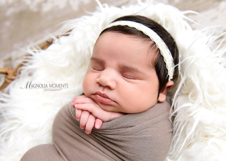 Newborn baby girl wrapped in taupe with cream headband posed in basket on barn floor with hands under chin during her newborn photo session by Evan Pollock of Magnolia Moments Photography who does professional photography near me. Philadelphia Newborn Photography Session.