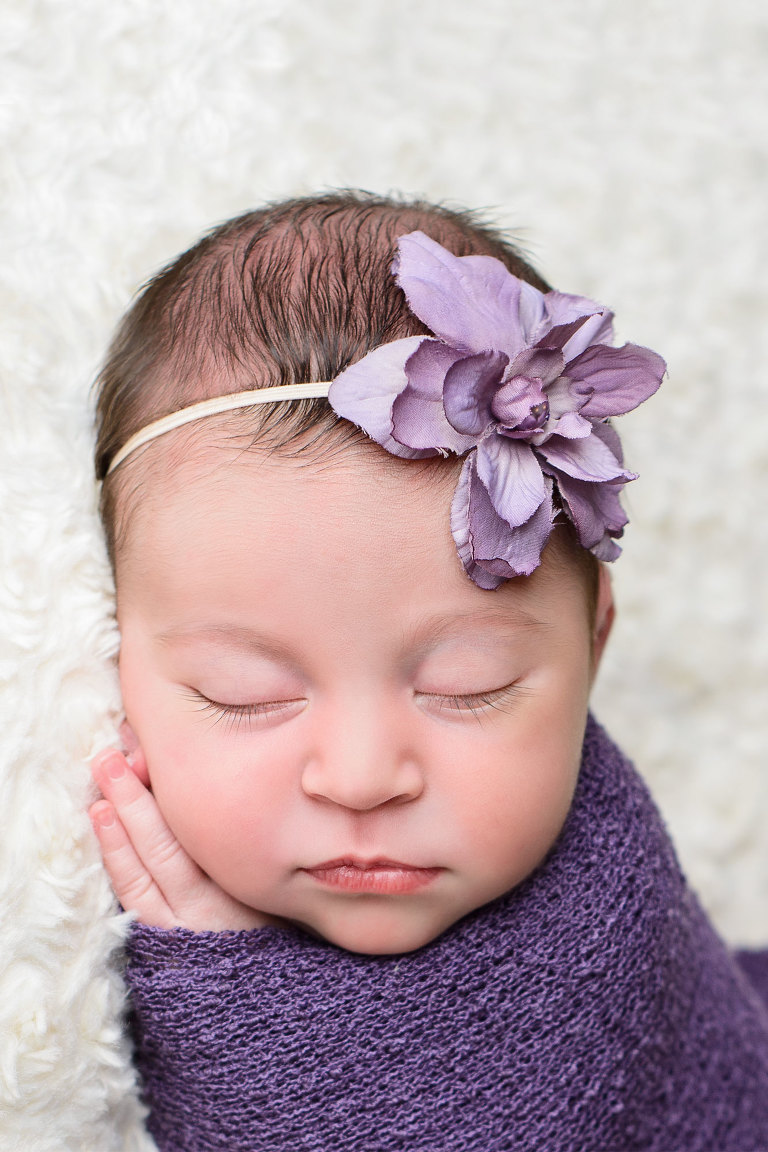 Close up portrait of swaddled baby girl in purple wrap with purple flower in hair by Evan Pollock of Magnolia Moments Photography in Philadelphia Pennsylvania