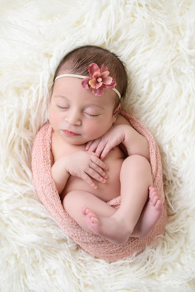 One of the best professional portrait of newborn baby girl swaddled in pink egg wrap on fur background by Evan Pollock of Magnolia Moments Photography in Philadelphia Pennsylvania