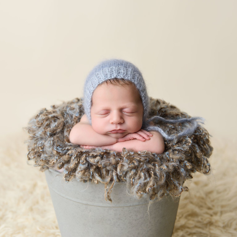 Professional portrait of newborn baby boy propped in bucket by Evan Pollock of Magnolia Moments Photography in Collegeville Pennsylvania