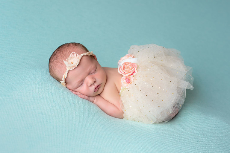 Newborn Baby Photography Near Me beautiful baby girl on teal background wearing white flowered tutu by Evan Pollock Professional Photographer at Magnolia Moments photography in her newborn studio